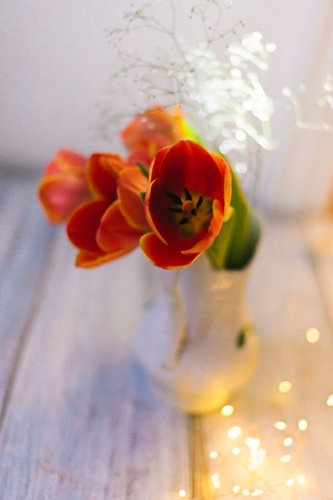 Tulips in a vase on a wooden background.