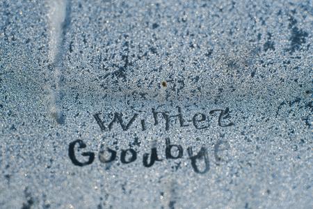 The inscription: goodbye, winter. On a frozen winter window in frosty patterns. Stock Photo