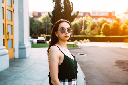 Brunette girl in a summer day in the city wearing round sunglasses.