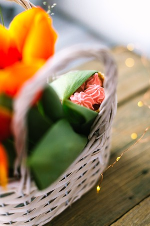 Tulips in a white basket on a wooden background with garlands in the background. Stock Photo