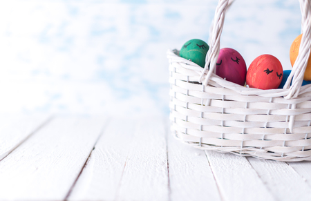 Easter eggs in a white basket on a wooden background.