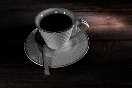 Cup of coffee on a dark wooden background.