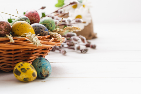 Easter eggs in a basket on a white wooden background.