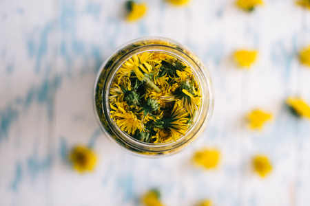 Dandelions in a glass jar on a white background. Stock Photo