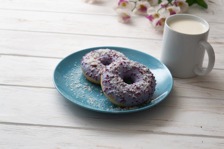 Donuts on a blue plate with a cup of milk on a white wooden background.