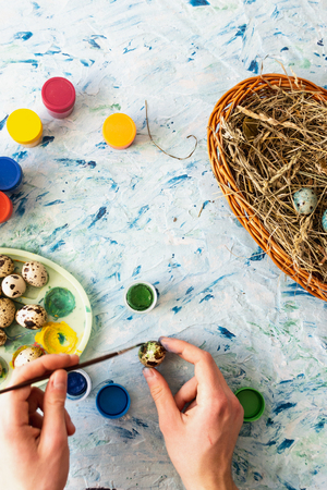 Painting Easter quail eggs on a light multi-colored background. Flat lay. Stock Photo