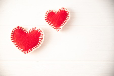 Red knitted soft fabric hearts on white background.