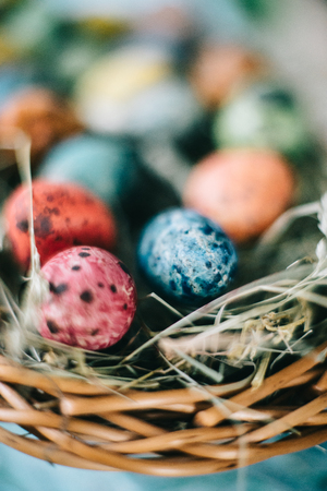 Quail Easter eggs in a basket on the hay. Easter concept. Stock Photo