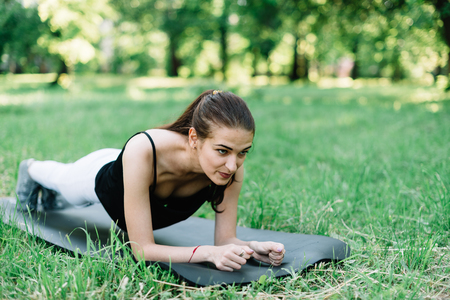 The girl does exercise the bar on the nature on the mat. Stock Photo