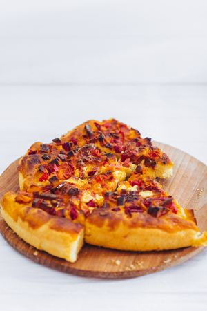 Homemade pizza on white wooden background on kitchen board. 스톡 콘텐츠
