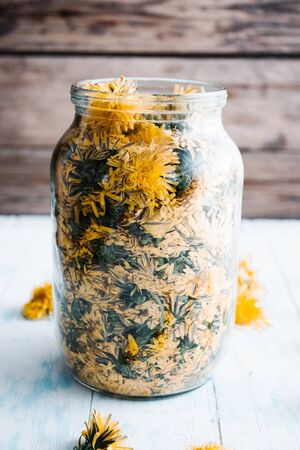 A glass jar filled with dandelion flowers and honey, to prepare homemade herbal syrup Stok Fotoğraf