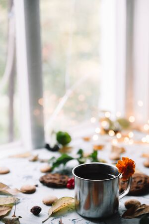 Cup with tea near the window with autumn leaves and cookies.