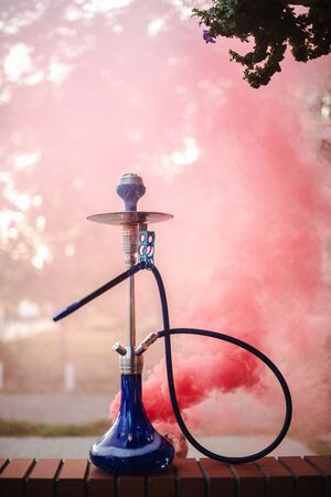 Hookah outdoors on a background of colored smoke. Banco de Imagens