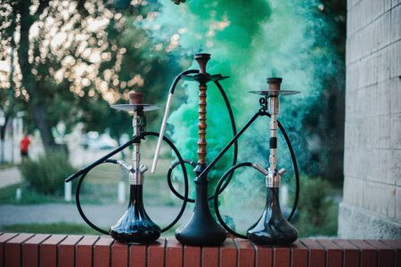 Hookah outdoors on a background of colored smoke. Stock fotó