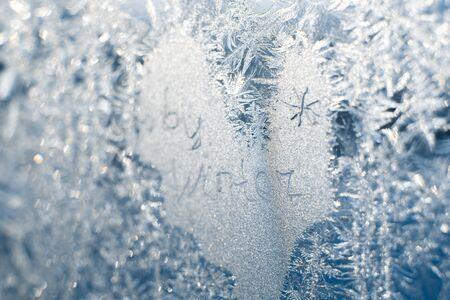The inscription: goodbye, winter. On a frozen winter window in frosty patterns.