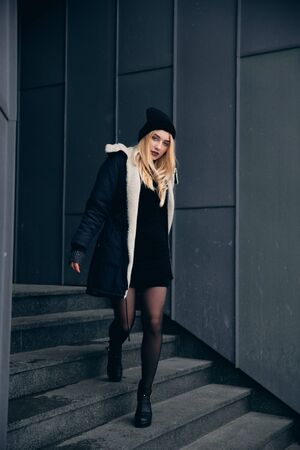 Girl in a black dress in the winter on a background of a dark building.