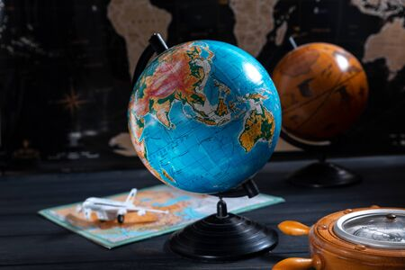Globe with a barometer and a small plane on the background of a black world map.