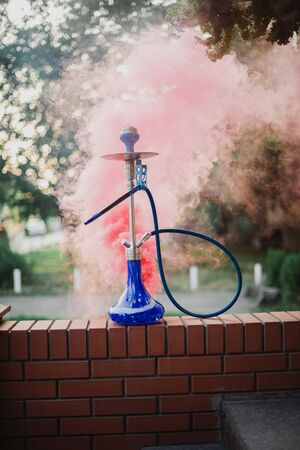 Hookah outdoors on a background of colored smoke. Imagens