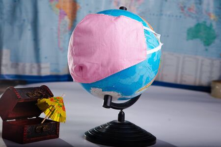 Globe in a medical mask on the background of a blurred world map concept of the global pandemic.