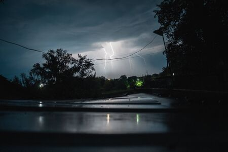 Summer night thunderstorm with powerful lightning in the village.