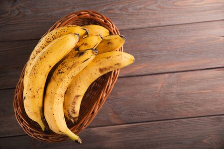 Bananas in a basket on a wooden brown natural background.