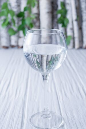 Water in a glass on a wooden background on a background of birch branches.