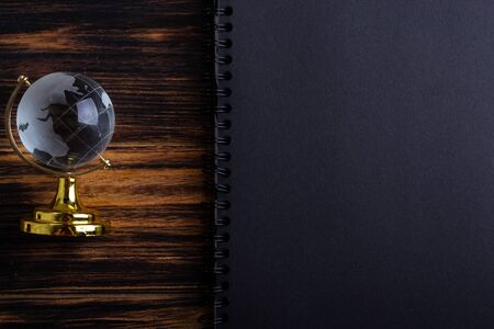 Glass globe on a black matte notebook on a wooden background.