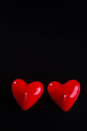 Red scented candles hearts on a black background.
