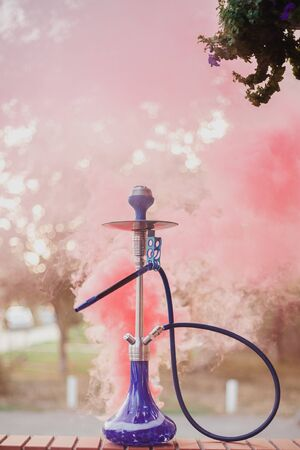 Hookah outdoors on a background of colored smoke. Archivio Fotografico - 148398769
