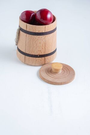 Sweet cherry berries in a wooden small barrel on a white background isolate. Archivio Fotografico