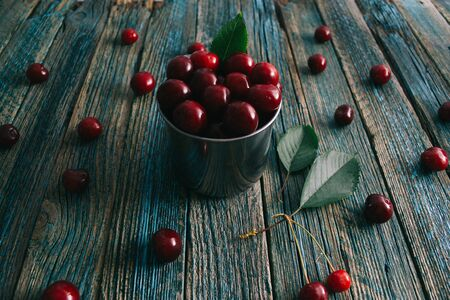 Cherries in a steel mug on a wooden background. Archivio Fotografico - 148489755