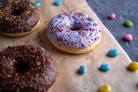 Donuts on a wooden board on a blue concrete background. Archivio Fotografico - 148398778