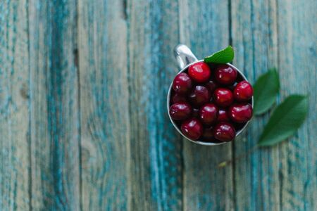 Cherries in a steel mug on a wooden background. Archivio Fotografico - 149044777