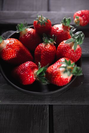Fresh ripe strawberries on a black wooden background.