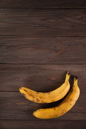 Bananas in a basket on a wooden brown natural background. Archivio Fotografico - 149044495