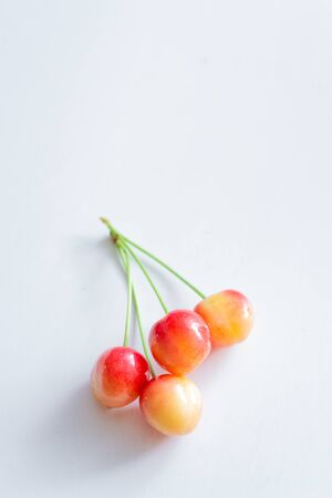Sweet cherry berries on a white paper background isolate.
