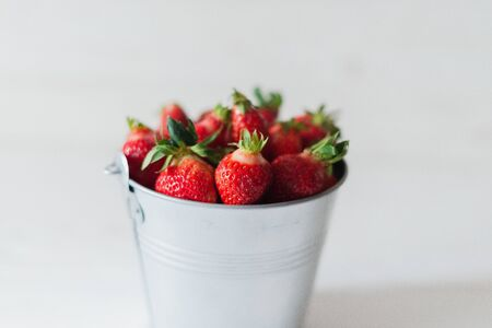 Juicy fresh strawberries in a metal bucket on a white background. Archivio Fotografico - 149044779