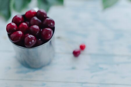 Cherries in a steel mug on a wooden background. Archivio Fotografico - 149044413