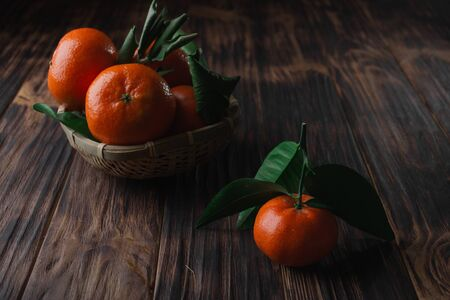 Fresh tangerines with leaves on a wooden old background. Archivio Fotografico - 149044624