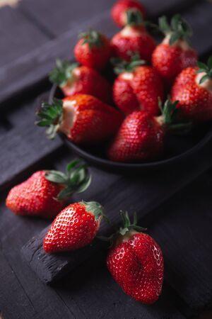 Fresh ripe strawberries on a black wooden background. Archivio Fotografico - 149044768