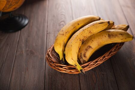 Bananas in a basket on a wooden brown natural background. Archivio Fotografico - 149044447