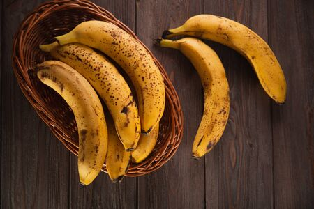 Bananas in a basket on a wooden brown natural background. Archivio Fotografico - 149044781
