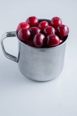 Sweet cherries in a steel mug on a white paper background. Archivio Fotografico - 149592239