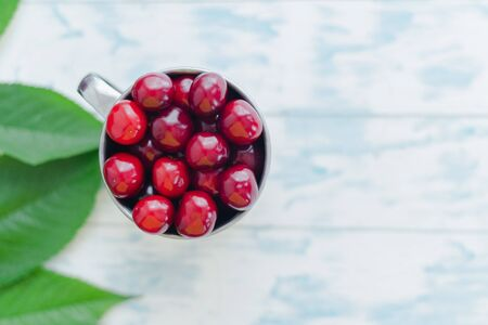 Cherries in a steel mug on a wooden background. Archivio Fotografico - 149044375