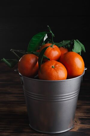 Fresh tangerines with leaves in a bucket on a wooden old background. Archivio Fotografico - 149050757