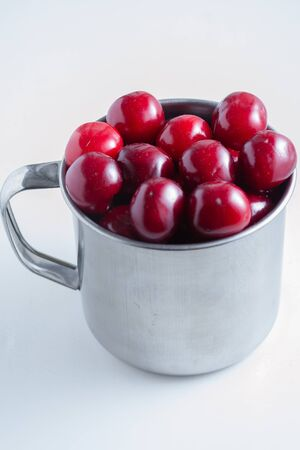 Sweet cherries in a steel mug on a white paper background. Archivio Fotografico - 149592243