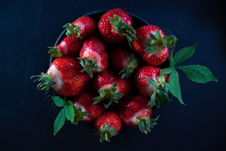 Fresh juicy strawberries in a black plate on a black matte background. Archivio Fotografico - 149051230