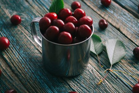 Cherries in a steel mug on a wooden background. Archivio Fotografico - 149139016