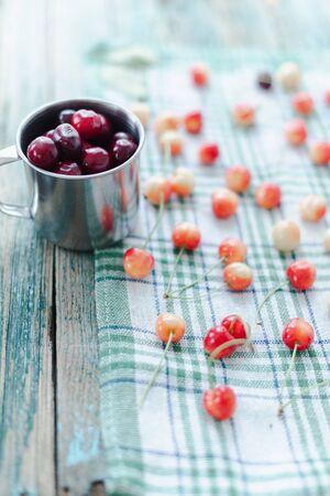 Cherries in a steel mug on a fabric background. Archivio Fotografico - 149050728