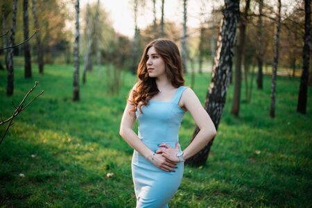 Beautiful young girl in a blue dress in a spring park. Stok Fotoğraf